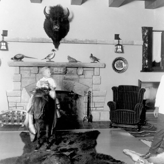"Waite Phillips' son, Elliot Waite ""Chope"" Phillips, photographed sitting atop his favorite pony in the Mansion's living room, circa 1920-1926."